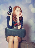 Redhead girl with binocular sitting on the big suitcase — Stock Photo