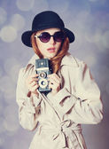 Redhead girl in cloak with camera as a spy — Stock Photo