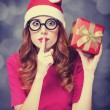 Redhead girl in christmas hat with gift. — Stock Photo #31355629
