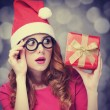 Redhead girl in christmas hat with gift. — Photo