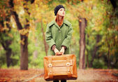 Redhead girl with suitcase at autumn outdoor. — Stock Photo