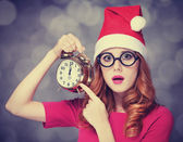 Redhead girl in christmas hat with clock — Stock Photo