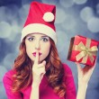 Redhead girl in christmas hat with gift. — Foto de Stock