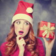 Redhead girl in christmas hat with gift. — ストック写真