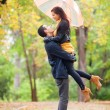 Ten couple with umbrella at the park in autumn time — Stock Photo