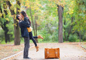 Couple with suitcase kissing at alley in the park — Stock Photo
