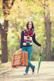 Brunette girl holding suitcase and umbrella at autumn alley in t — Stock Photo