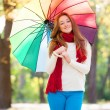 Teen girl in red scarf with umbrella at autumn outdoor — Stock Photo