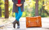 Women's foots near suitcase at autumn outdoor. — Stock Photo