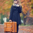 Blonde girl with suitcase at outdoor. — Stock Photo