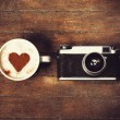 Cup of coffee with retro camera — Stock Photo