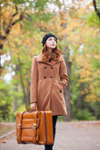 Redhead girl with suitcase at autumn outdoor — Stock Photo