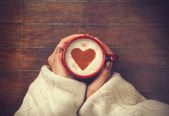 woman holding hot cup of coffee, with heart shape — 图库照片