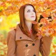 Redhead girl in autumn park — Stock Photo