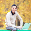 Programmer with notebook sitting in autumn park — Foto Stock