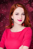 Girl with christmas earrings on red background isolated — Stok fotoğraf
