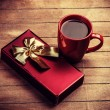 Gift and cup of coffee on wooden table — Stock Photo