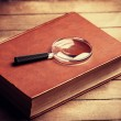 Loupa and book on wooden table — Stock Photo