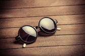 Retro sunglasses on wooden table — Stock Photo