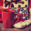 Cup of coffee and gifts at background — Stockfoto