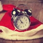 Retro alarm clock on table with christmas hat — Stock Photo