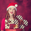 Redhead girl with gifts on red background — Stock Photo