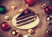 Chocolate cake and christmas gifts at background — Stock Photo