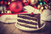 Chocolate cake and chritmas gifts at background — Stock Photo