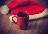Cup of coffee and red hat. — Stock Photo