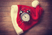 Retro alarm clock on table with christmas hat — 图库照片