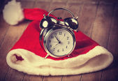 Retro alarm clock on table with christmas hat — Zdjęcie stockowe