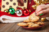 Female hand holding cookie at christmas gift background — Stock Photo