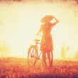 Girl on a bike in the countryside in sunrise time. — Stock Photo #36879711