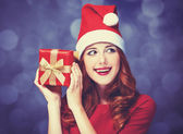 Redhead girl with gifts on purple background — Stock Photo