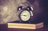 Alarm clock and book. Photo in old color image style. — ストック写真