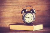 Alarm clock and book. Photo in old color image style. — Stock Photo