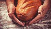 Baker's hands with a bread. Photo with high contrast — Stock Photo