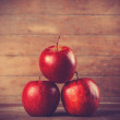 Stock Photo: Three red apples on wooden table. Photo in retro color style.