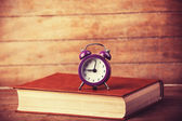 Alarm clock and book. — Stock Photo