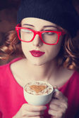 Redhead girl in glasses with cup of coffee. — Zdjęcie stockowe
