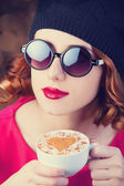Redhead girl in glasses with cup of coffee. — Stock Photo