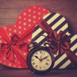 Retro clock and gift in heart shape on the background. — Stock Photo #38658561
