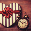 Retro clock and gift in heart shape on the background. — Stock Photo #38658571