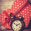Stock Photo: Retro clock and gift in heart shape on the background.