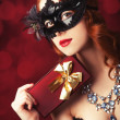 Beautiful women in carnival mask with gift. — Stock Photo