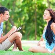 Young students sitting on green grass with note book. — Stock Photo #38658715