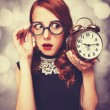 Surprised redhead girl with clock. — Zdjęcie stockowe