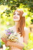 Redhead girl with flowers at outdoor. — Stock Photo