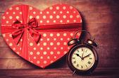 Retro klok en cadeau in hart vorm op de achtergrond. — Stockfoto