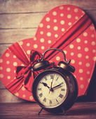 Retro clock and gift in heart shape on the background. — Stock Photo